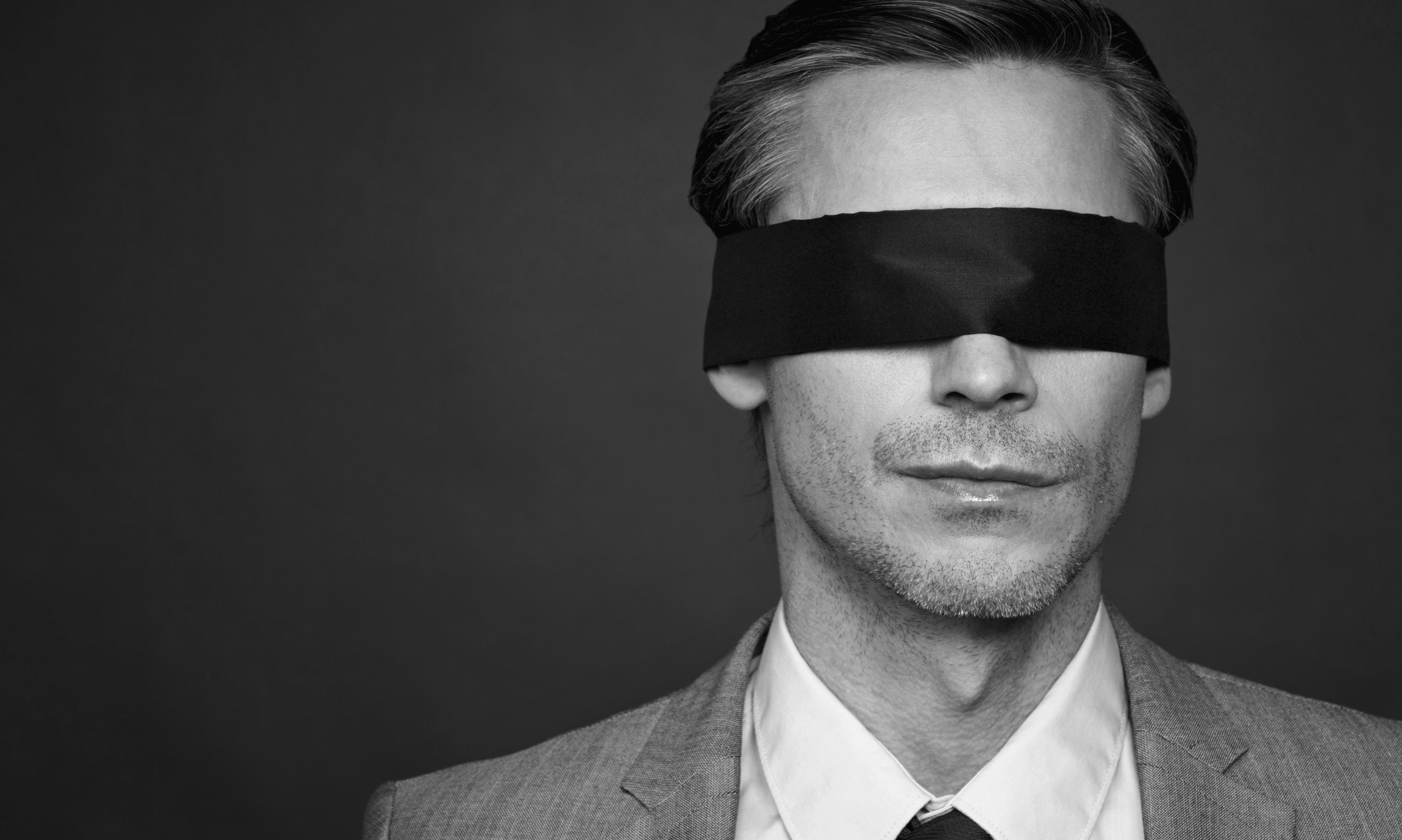 Closeup of man in suit and tie wearing blindfold